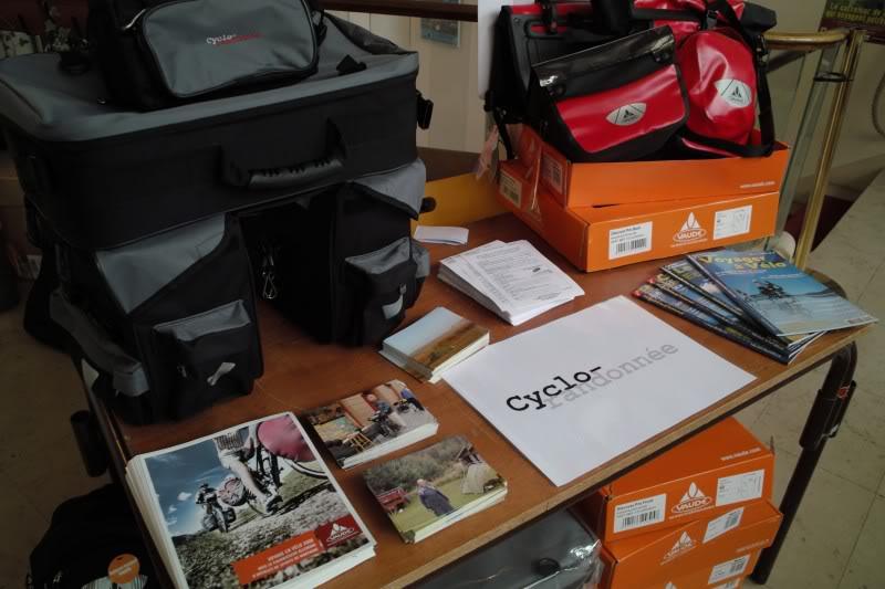 Présentation de matériel pour voyager à vélo au festival Culture Aventure : sacoche, remorque, tente, veste étanche et respirante.