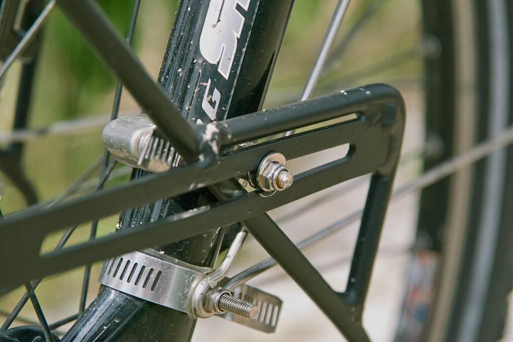 Montage d'un porte-bagage avant sur une fourche suspendue à l'aide de colliers de serrage.