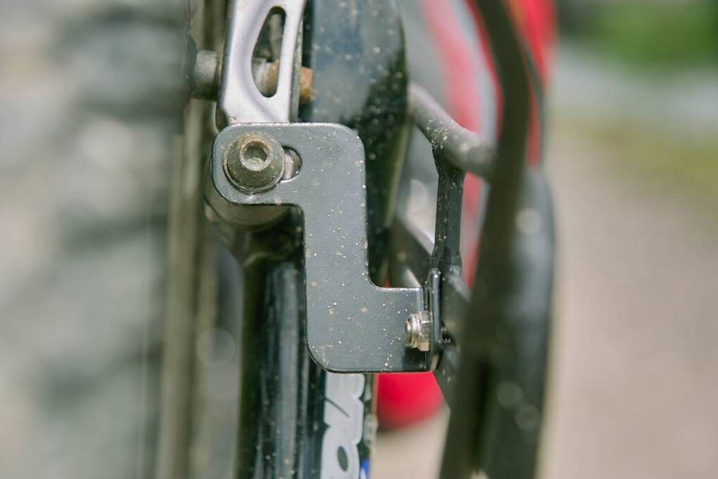 Montage d'un porte-bagage avant aux supports de freins V-brake sur une fourche suspendue.
